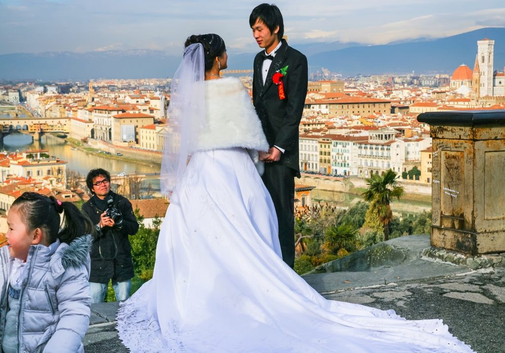 groom-and-bride-during-wedding-ceremony-on-Piazzale-Michelangelo-in-Florence-city-in-sunny-winter-day
